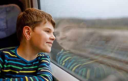 電車内の座席から窓を通して外を眺める少年のイメージ