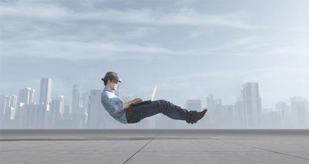 仕事が楽すぎて空中に浮いた人がパソコン作業するイメージ